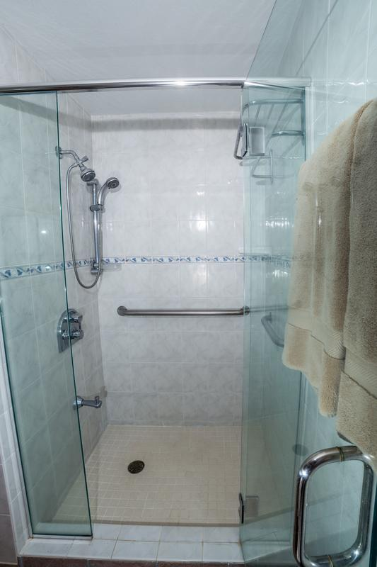 Roomy shower includes standard and handheld shower heads along with safety grab bars.