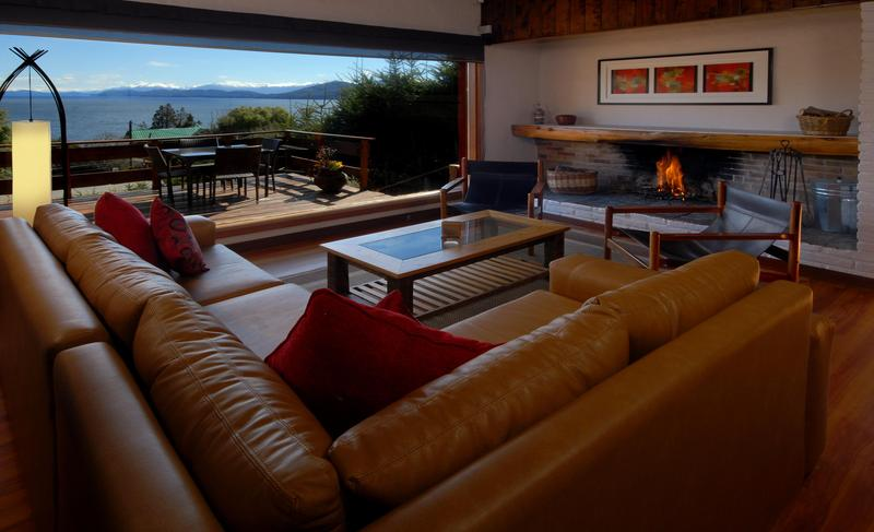 Living room with comfy new sofa, open fireplace and great views of Lake Nahuel Huapi and Patagonian skies.