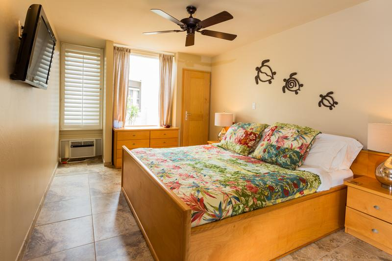 Tiled bedroom features A/C, ceiling fan and flat screen TV.